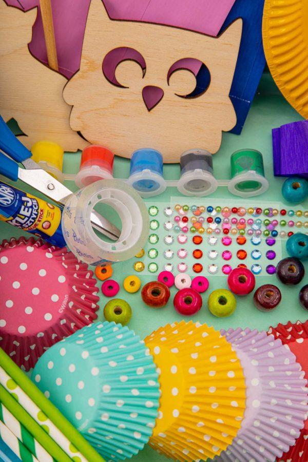 kolorowe koraliki, kolorowe papilotki, drewniane elementy, farbki, nożyczki i taśma