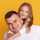 Portrait of happy father and beautiful little girl wering white t shirts and jeans, posing isolated over yellow studio background, have happy facial expression, spending time together. Family concept.
