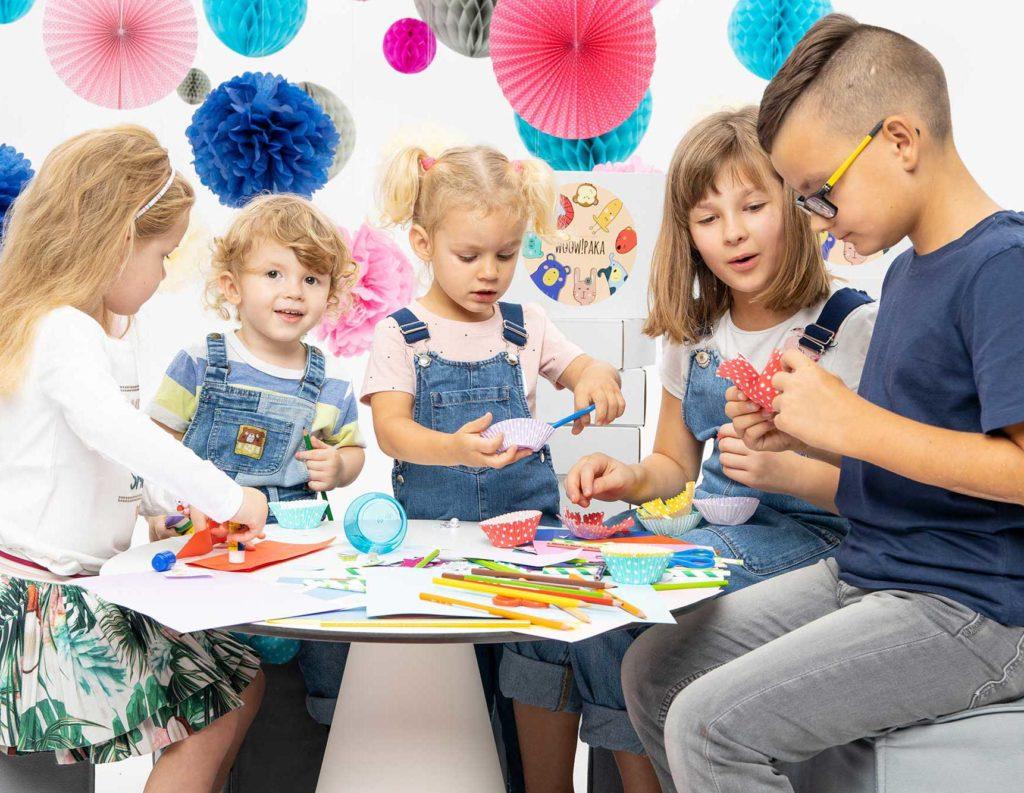 dzieci siedzące przy stole bawiące się zabawami z woowpaki